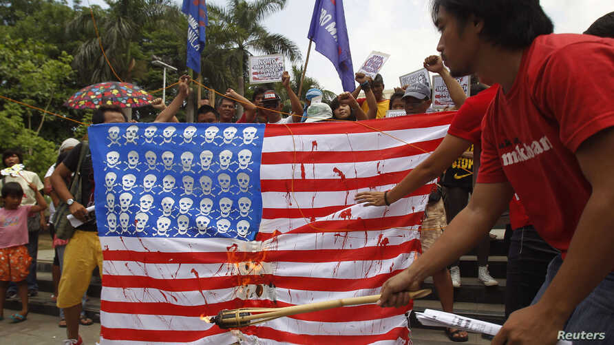 A protester burns a mock U.S. flag during a protest in Manila, April 25, 2014.