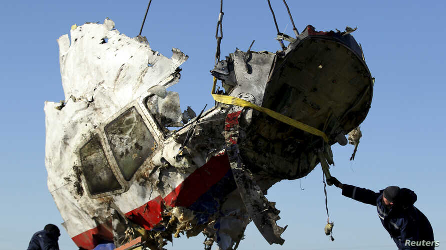 Local workers transport a piece of the Malaysia Airlines flight MH17 wreckage at the site of the plane crash near the village of Hrabove (Grabovo) in Donetsk region, eastern Ukraine, Nov. 20, 2014.