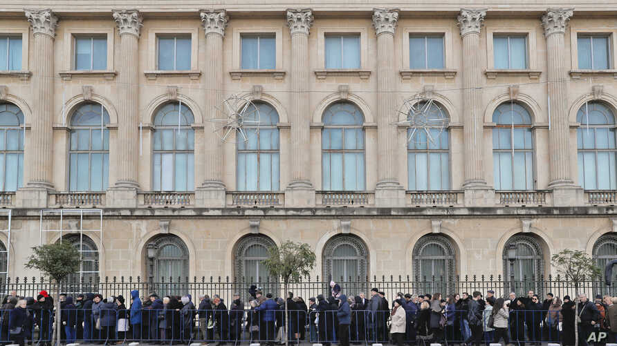 People wait outside the former royal palace to pay respects to the late Romanian King Michael in Bucharest, Romania, Dec. 14, 2017.