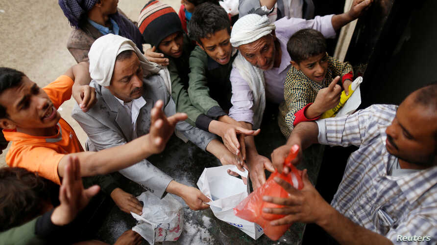 FILE - People gather to collect food rations at a food distribution center in Sana'a, Yemen, March 21, 2017.