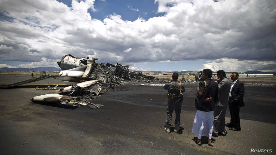 Airport officials look at the wreckage of a military transport aircraft destroyed by Saudi-led airstrikes, at the Sanaa International Airport, in Yemen, May 5, 2015.
