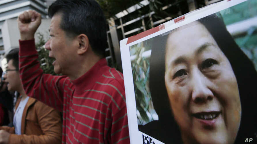 FILE - Anti-Beijing protesters hold picture of veteran Chinese journalist Gao Yu during a rally outside Chinese central government's liaison office in Hong Kong.