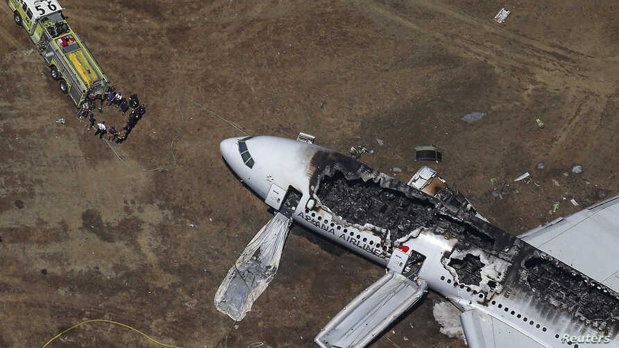 Rescue officials stand near an Asiana Airlines Boeing 777 plane after it crashed while landing at San Francisco International Airport in California, July 6, 2013.
