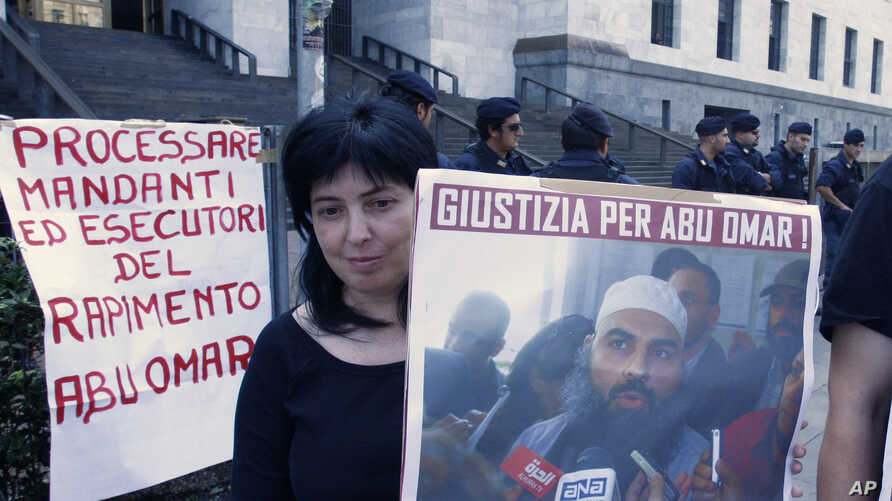 """FILE - A protester holds up a poster with writing reading in Italian """"Justice for Abu Omar"""" above a picture of Muslim cleric Osama Moustafa Hassan Nasr, also known as Abu Omar, outside Milan's court house while the trial of 26 Americans and seven Ita"""