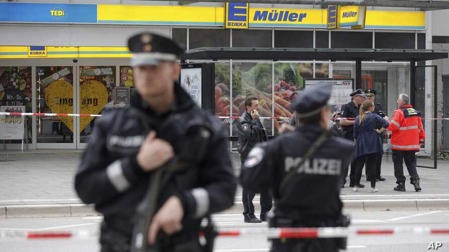 Police officers secure the area after a knife attack at a supermarket in Hamburg, Germany, July 28, 2017.