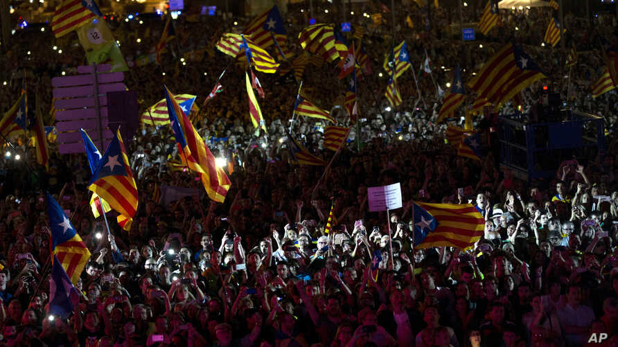 People cheer and wave esteledas, or Catalonia independence flags, during the 'Yes' vote closing campaign in Barcelona, Spain,  Sept. 29, 2017.