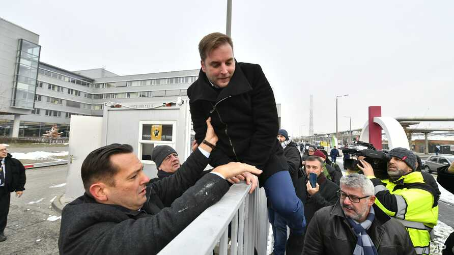 Parliamentary deputy of the oppositional Hungarian Socialist Party MSZP Zsolt Molnar, left, helps MSZP deputy Tamas Harangozo climb the fence of the public broadcaster MTVA in Budapest, Hungary, Dec. 17, 2018.