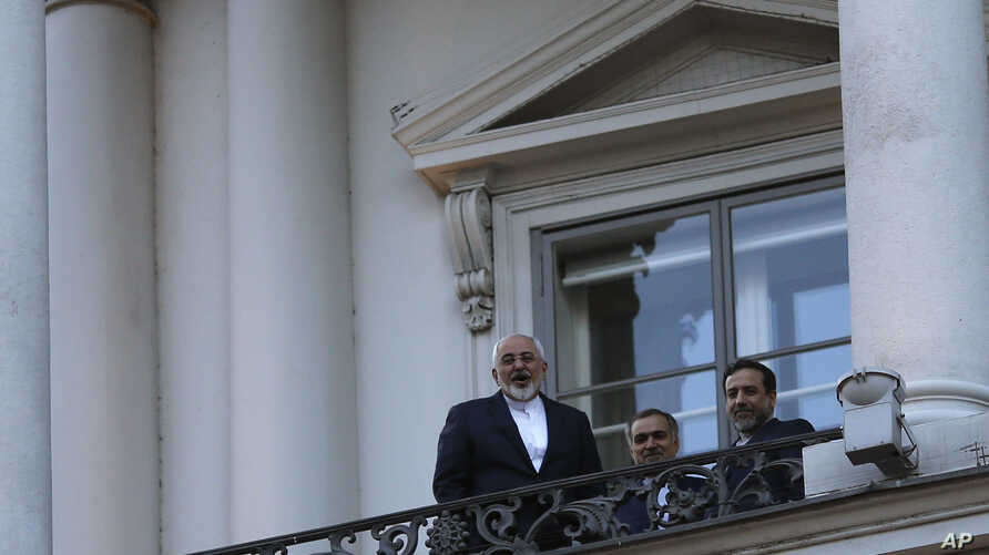 Iranian Foreign Minister Mohammad Javad Zarif (L) talks to journalist from a balcony of the Palais Coburg hotel where the Iran nuclear talks are being held in Vienna, Austria, July 9, 2015.