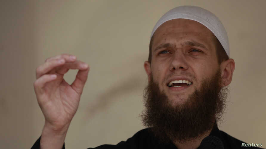 FILE - Islamist preacher Sven Lau delivers a speech during a pro-Islam demonstration in Cologne, Germany, June 9, 2012.