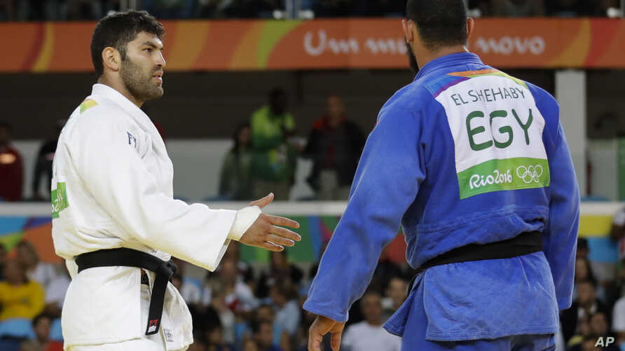 Egypt's Islam El Shehaby, blue, declines to shake hands with Israel's Or Sasson, white, after losing during the men's over 100-kg judo competition at the 2016 Summer Olympics in Rio de Janeiro, Brazil, Friday, Aug. 12, 2016.