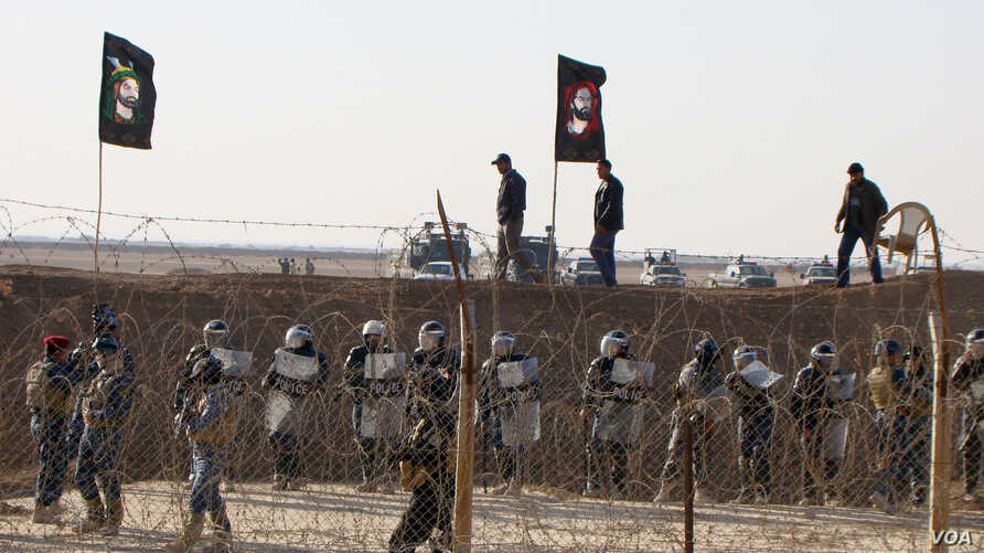 In this December 9, 2011, photo provided by the People's Mujahedeen Organization of Iran, Iraqi police stand guard outside Camp Ashraf northeast of Baghdad (image authenticity cannot be independently verified).