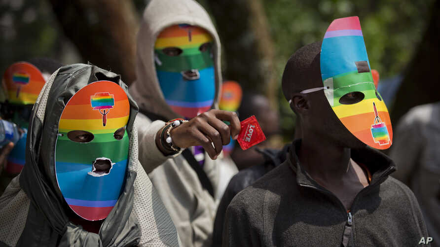 Kenyan gays and lesbians and others supporting their cause wear masks to preserve their anonymity and one holds out a wrapped condom, as they stage a rare protest, against Uganda's increasingly tough stance against homosexuality and in solidarity wit