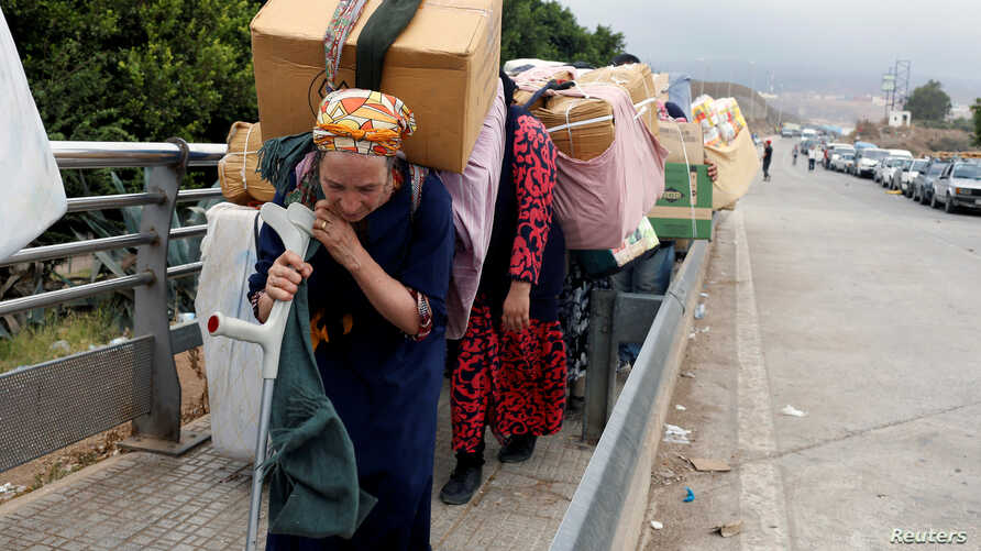 FILE - Moroccan women carry goods to be taken across the border from Spain's North African enclave of Melilla into Moroccan settlement of Beni Ansar, in Melilla, Spain, July 18, 2017.