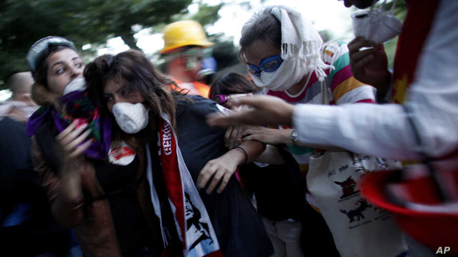 FILE - In this June 11, 2013, photo, a protester affected by tear gas is helped by other protesters to a field hospital in Gezi Park in Taksim Square in Istanbul, Turkey.