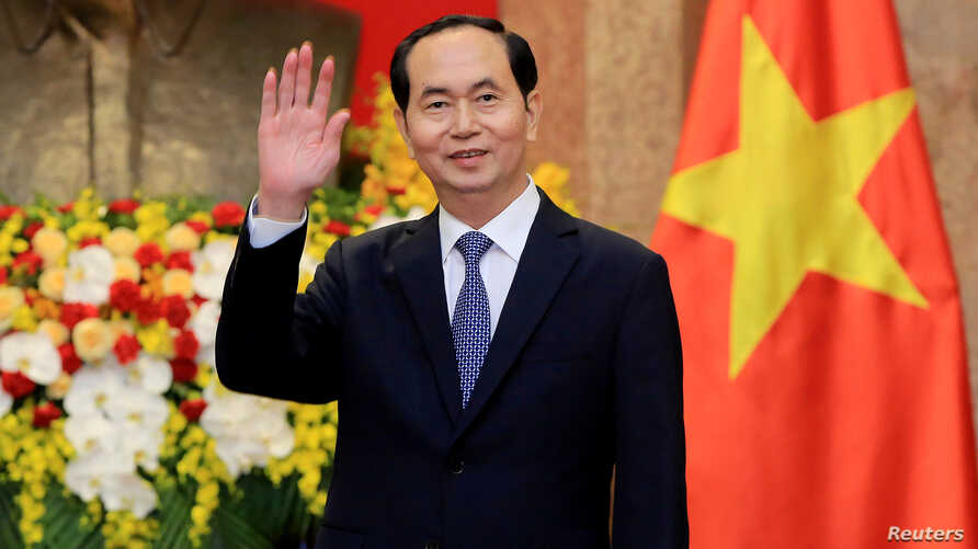 FILE - Vietnamese President Tran Dai Quang greets journalists as he waits for the arrival of Russian Foreign Minister Sergei Lavrov at the Presidential Palace in Hanoi, Vietnam, March 23, 2018.