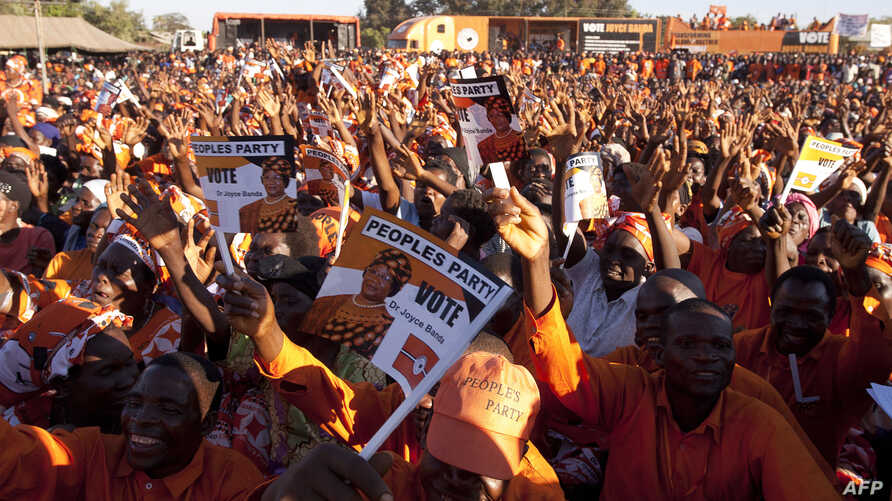 Supporters of Malawi's incumbent President cheer during her final campaign rally at Songani village on the outskirts of the city of Zomba, the former capital of Malawi, May 17, 2014.