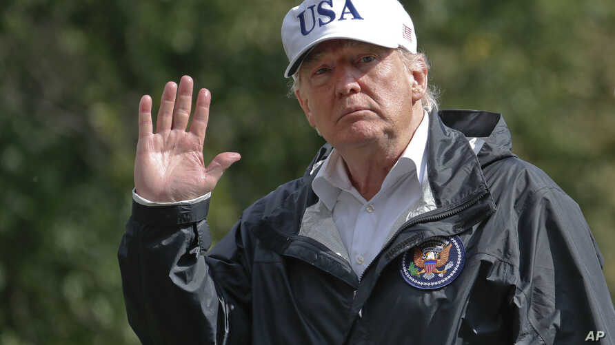 President Donald Trump waves as he arrives at the White House, Sept. 14, 2017, in Washington. Trump is returning from Florida after viewing damage from Hurricane Irma.