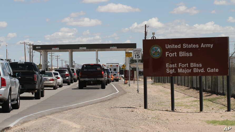 FILE - Cars wait to enter Fort Bliss in El Paso, Texas.