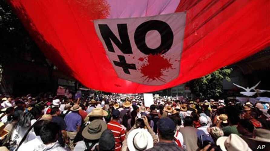 People carrying signs reading 'Stop the War' , ' No More Violence' and Mexican flags march against gang violence in Mexico City,  May 8, 2011