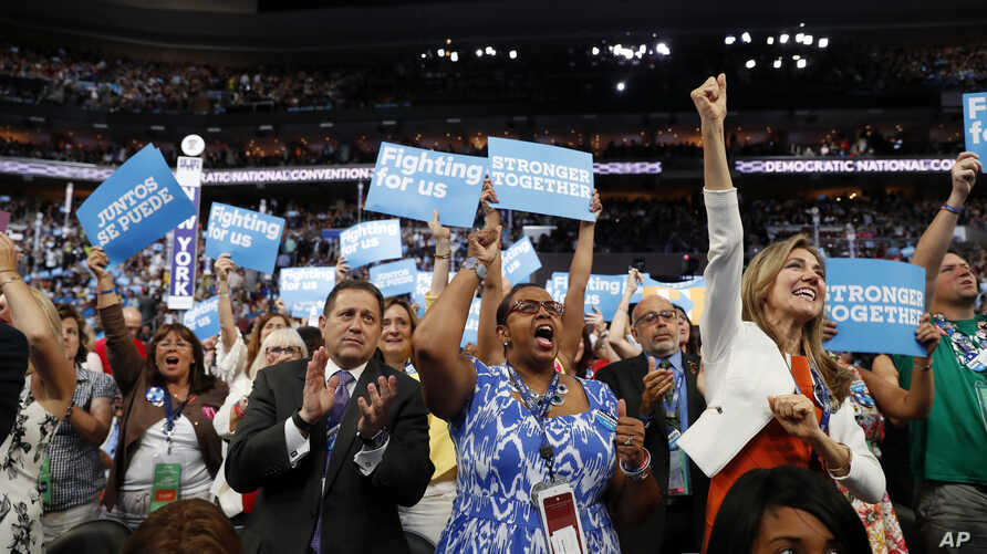 New York delegates cheer as they hold up signs during the second day session of the Democratic National Convention in Philadelphia, July 26, 2016.