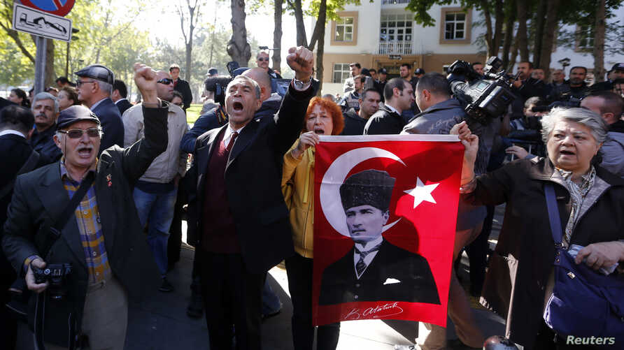Relatives of detained military officers hold a portrait of Mustafa Kemal Ataturk, founder of modern Turkey, and  shout slogans in front of a courthouse in Ankara October 9, 2013.