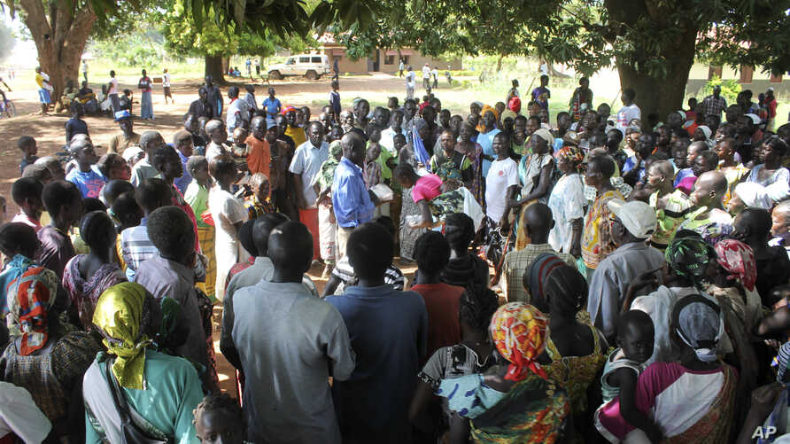 FILE - A U.N. refugee agency official speaks to civilians during a distribution of food items in Yei, in southern South Sudan, Nov. 15, 2016. The formerly peaceful town of Yei became a center of country's renewed civil war, gripped by killings among