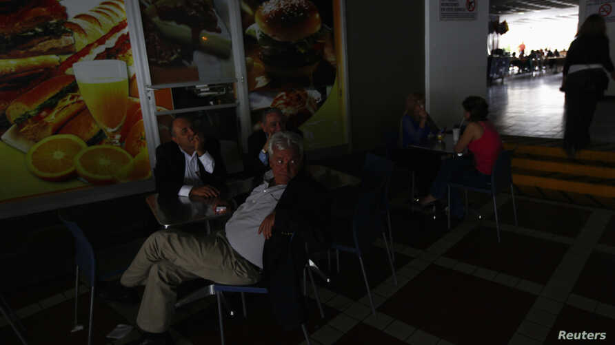 People sit down to have lunch in darkness, during a massive blackout in Caracas, Venezuela, Sept. 3, 2013.