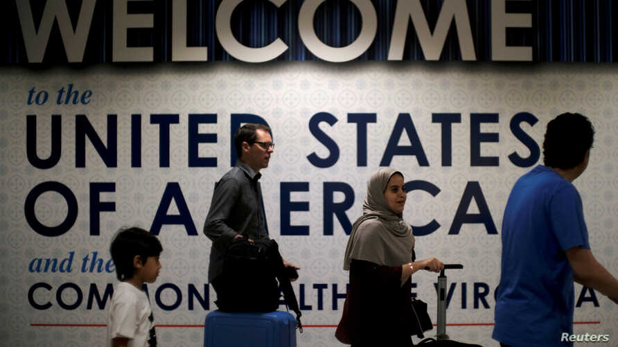 FILE: International passengers arrive at Washington Dulles International Airport after the U.S. Supreme Court granted parts of the Trump administration's emergency request to put its travel ban into effect later in the week pending further judicial r