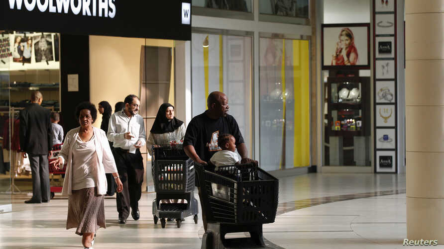 Shoppers leave a Woolworths store at a shopping centre in Lenasia, south of Johannesburg, Aug. 28, 2013.
