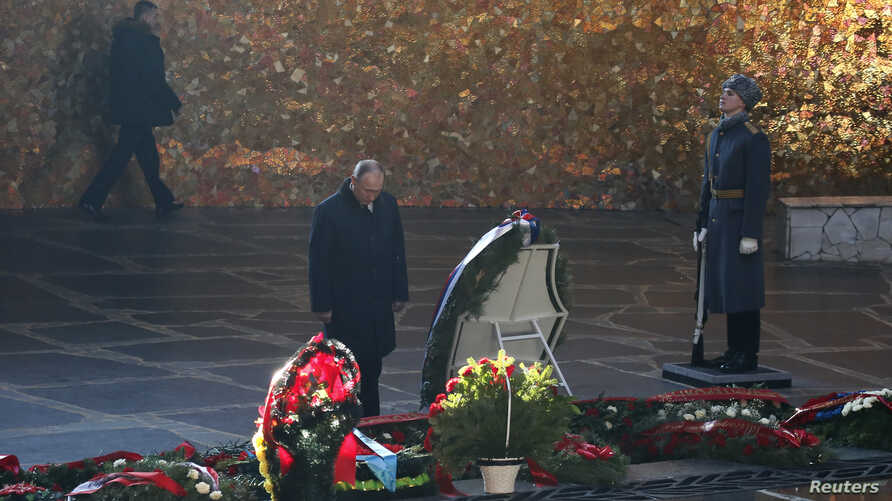 Russian President Vladimir Putin attends a wreath laying ceremony at the eternal flame during an event to commemorate the 75th anniversary of the battle of Stalingrad in World War Two, at the Mamayev Kurgan memorial complex in the city of Volgograd,