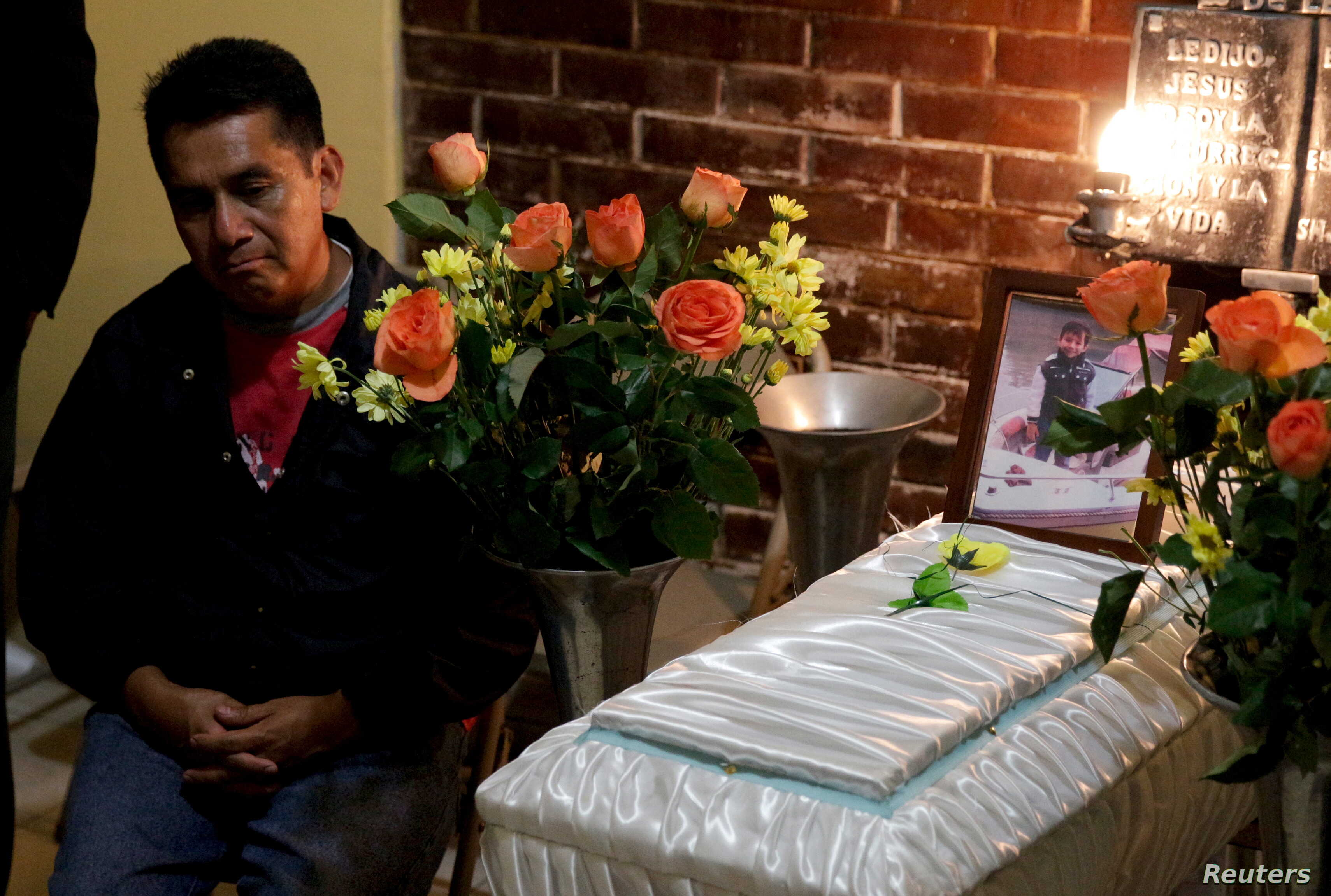 A man sits next to the coffin of mudslide victim Andres Gomez, 4, during his wake in Santa Catarina Pinula, on the outskirts of Guatemala City, Oct. 4, 2015.