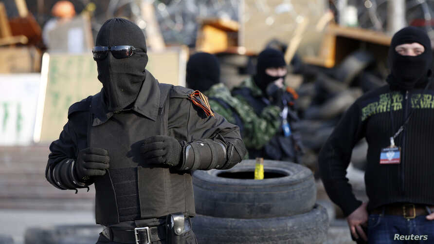 Masked pro-Russia militants stand guard outside a regional government building they seized in Donetsk, eastern Ukraine, April 22, 2014.