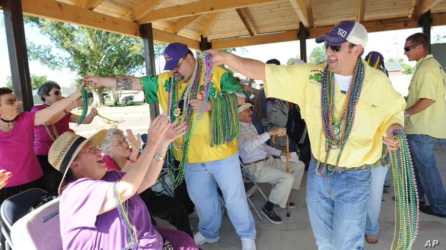 FILE - Senior citizens enjoy a Mardi Gras parade after they helped plant and build a new park after being awarded the Elations Boomers Building a Better America Grant in Houma, La.