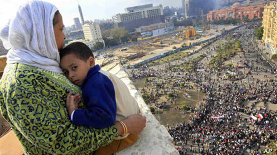 An Egyptian mother hugs her child as she watches thousands of Egyptian protesters gather at Tahrir square in Cairo, Egypt, Sunday, Jan. 30, 2011, with the ruling National Democratic party building burned at top right behind the red colored Egypt muse