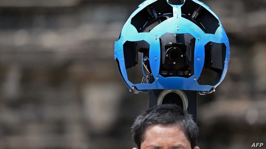 A Cambodian technician carries a back-packa mounted with a device housing 15 cameras as he demonstrates the technique used to digitally map the Angkor Wat temple, part of the Angkor architectural complex in north-western Cambodia on April 3, 2014.