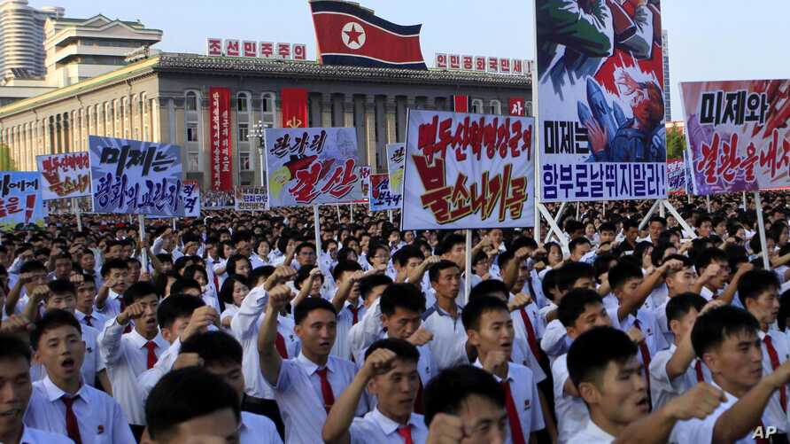 """FILE - Tens of thousands of North Koreans rally at Kim Il Sung Square carrying placards and propaganda slogans as a show of support against United Nations' sanctions, Aug. 9, 2017, in Pyongyang, North Korea. Propaganda poster second from right says """""""