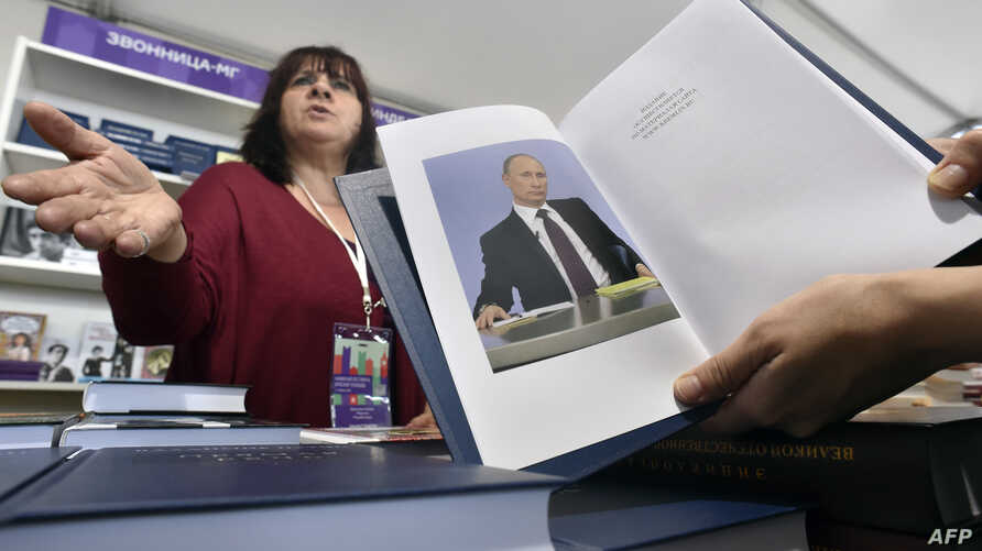 """A customer holds a copy of Russian President Vladimir Putin's book """"Direct speech"""" as she speaks with a vendor (L) at the Red Square Book Festival in Moscow on June 3, 2016."""
