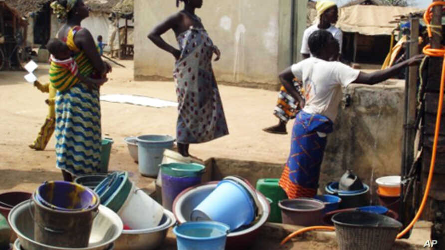 Ivorian women who have fled seen collecting water in Guiglo