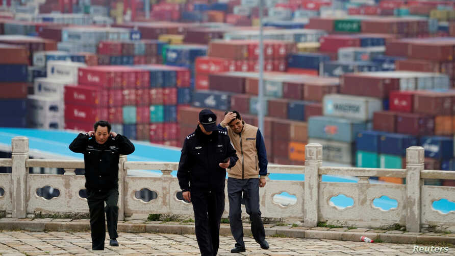 FILE - Security guards walk in front of containers at the Yangshan Deep Water Port in Shanghai, April 24, 2018.