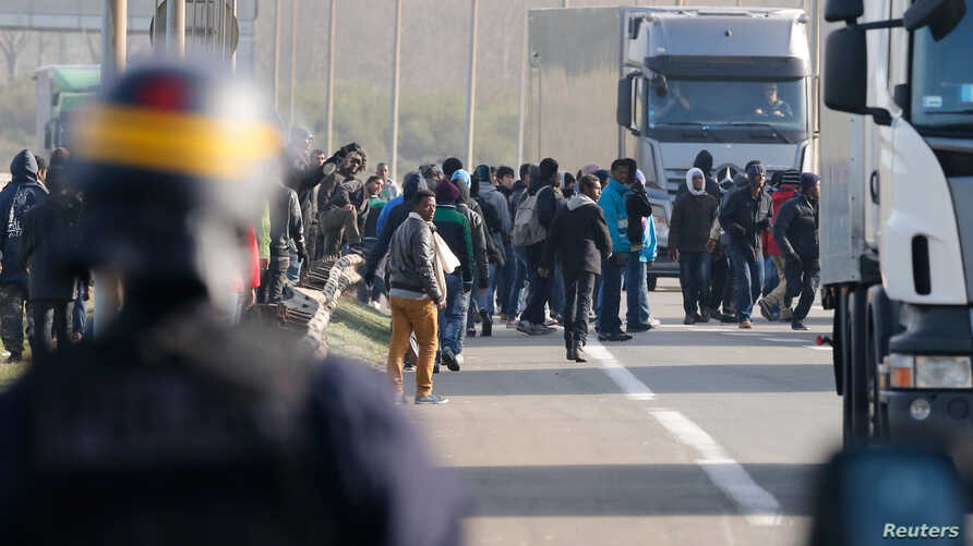 French riot police chase migrants from U.K.-bound lorries making their way to the ferry terminal in Calais, Oct. 22, 2014.