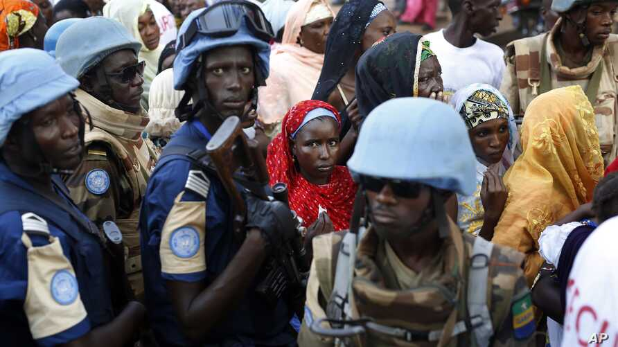 FILE- In this Nov. 30, 2015 file photo, UN soldiers stand near Muslims faithful queuing to enter the Central Mosque on the occasion of Pope Francis' visit, in Bangui's Muslim enclave of PK5, Central African Republic.
