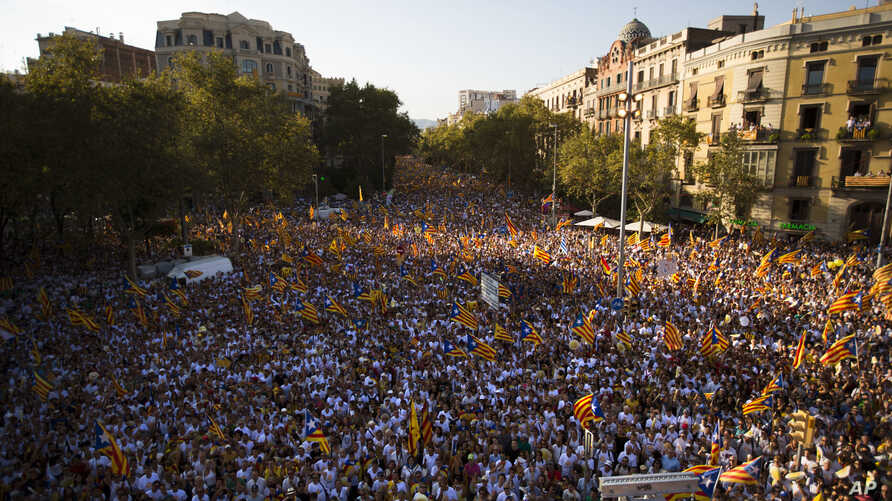 """Spain Catalonia Independence: People wave """"estelada"""" flags, that symbolize Catalonia's independence, during a demonstration calling for the independence of Catalonia, in Barcelona, Spain, Sunday, Sept. 11, 2016."""