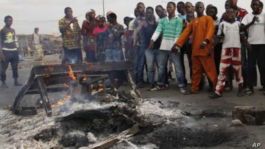 Supporters of Alassane Ouattara point to what they say are the burnt remains of three alleged soldiers loyal to president Laurent Gbagbo, in the Abobo district of Abidjan, Ivory Coast (File Photo - March 7, 2011)