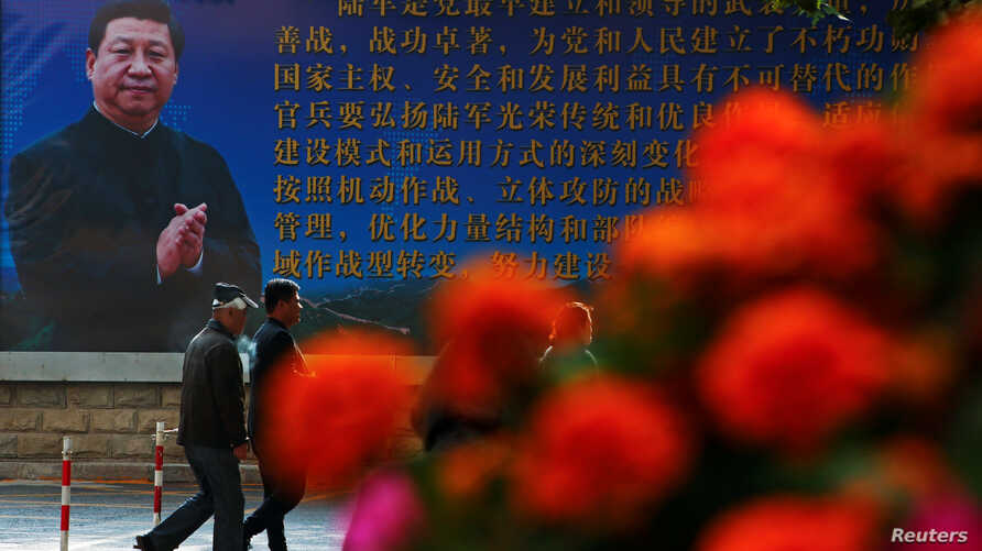 Men walk past a poster of the Chinese People's Liberation Army (PLA) featuring a portrait of President Xi Jinping, on the second day of plenary sessions of the 18th Central Committee of the Communist Party of China (CPC) in Beijing, Oct. 25, 2016.