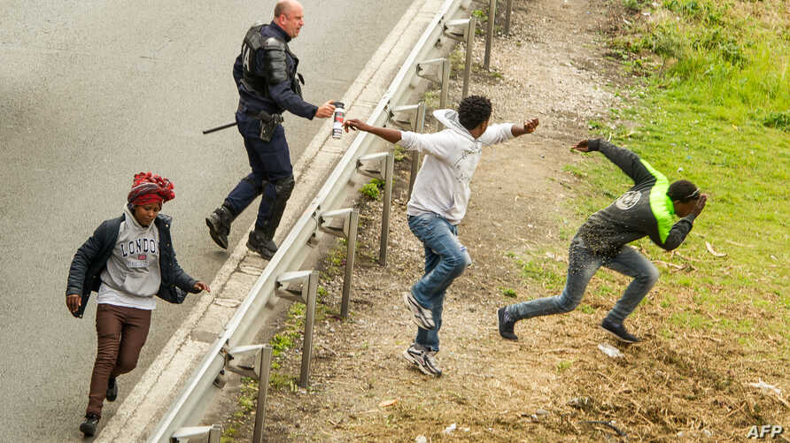 TOPSHOTSA police officer sprays tear gas to migrants trying to access the Channel Tunnel on the A16 highway on June 23, 2015 in Calais, northern France. AFP PHOTO PHILIPPE HUGUEN