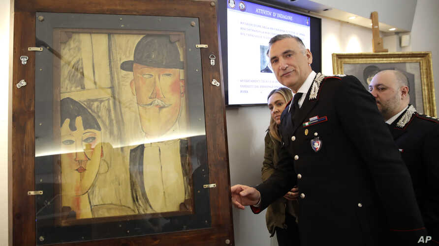 Carabinieri Lieutenant Colonel Nicola Candido stands by a painting attributed to 20th century Italian painter Amedeo Modigliani but determined to be a fake, during a press conference in central Rome, March 13, 2019.