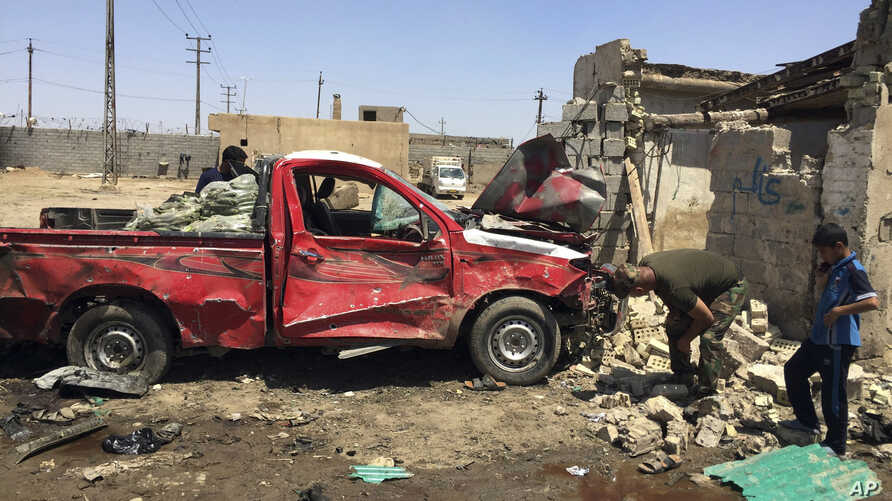 On April 30, 2016, residents inspect the scene of car bombing at an open-air market in Baghdad's suburb of Nahrawan, Iraq.