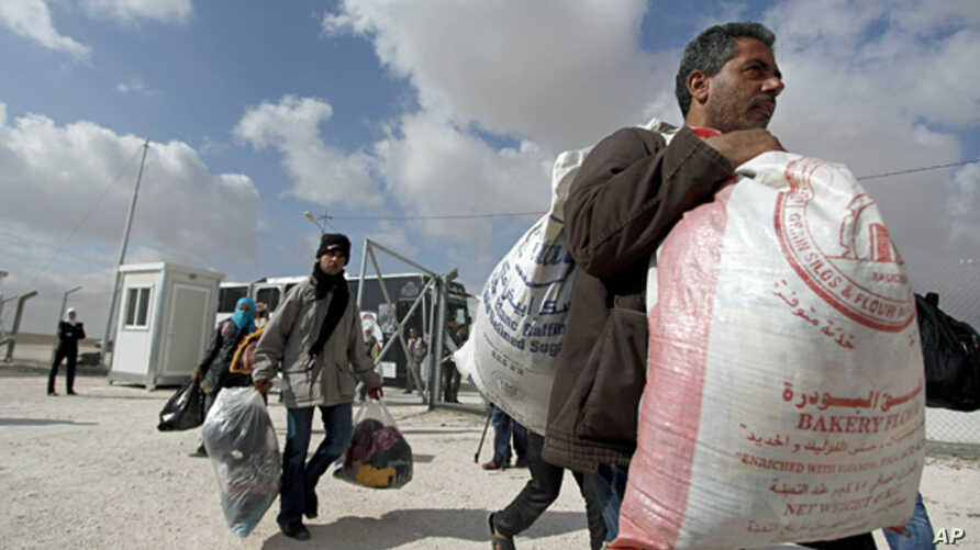 Newly-arrived Syrian refugees carry their belongings upon their arrival to the new Jordanian-Emirati refugee camp, Mrajeeb al-Fhood, in Zarqa, Jordan, April 10, 2013.
