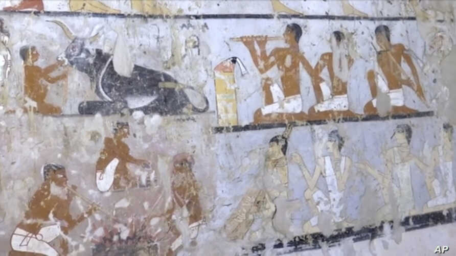 This image taken from video, Feb. 3, 2018, shows wall paintings inside a 4,400-year-old tomb near the pyramids outside Cairo, Egypt. Egypt's Antiquities Ministry announced the discovery Saturday and said the tomb likely belonged to a high-ranking off