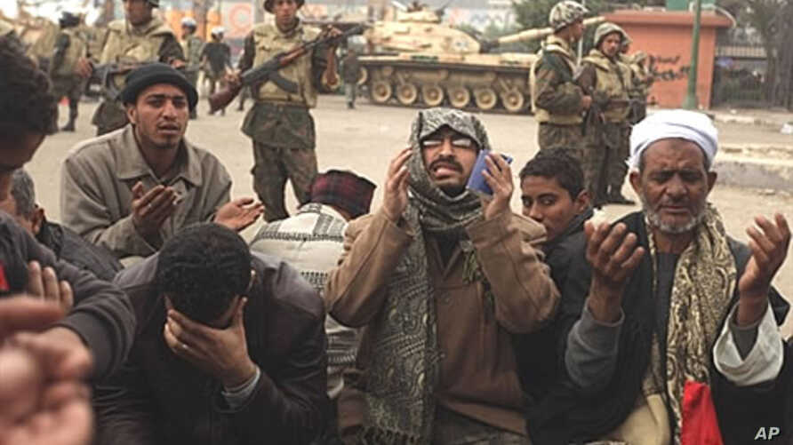Egyptian anti-government demonstrators and members of the Egyptian Muslim Brotherhood movement pray in front of Egyptian soldiers at Cairo's Tahrir Square, February 7, 2011